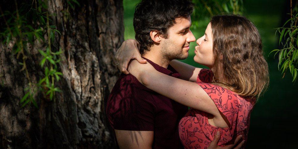 Předsvatební fotka snoubenců v zahradě pod stromem.