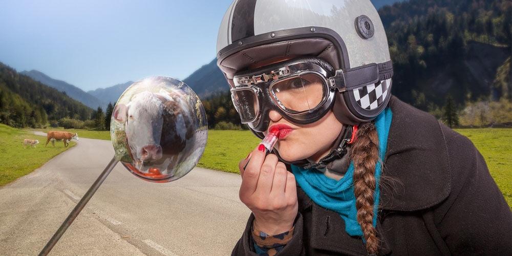 Nevěsta v helmě si maluje rty na motorce v polích. V zadu a okolo jsou krávy