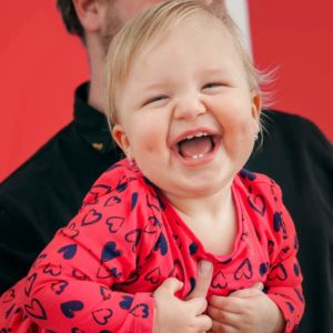 Malé dítě s směje. Otec ho drží na ruce a v pozadí je červená stěna