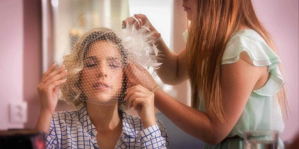 Nevěsta u kadeřnice finalizují účes a přípravy na svatební focení.