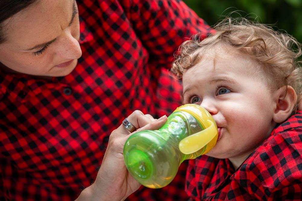 Dítě a maminka v červeném. Dítě pije ze zelené flašky.