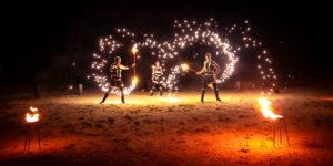 Tři členové Postrpoi s plameny na tyči.