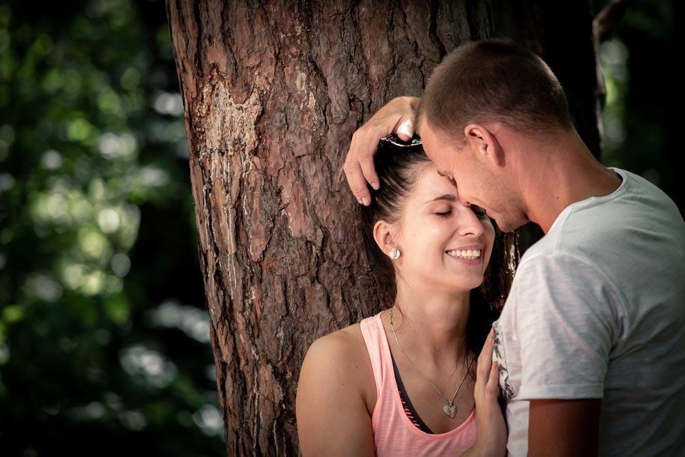 Dvojice v objetí u stromu v lese.