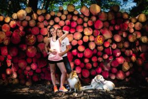Portrét snoubenců a dvou psů před kmeny stromů.