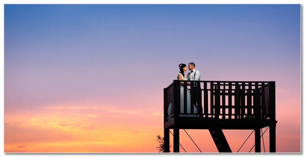 Ženich a nevěsta na vyhlidce při západu slunce.