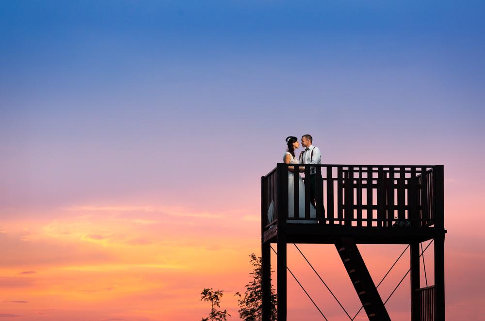 Nevěsta a ženich na rozhledně na ranči v Kostelach. při západu slunce