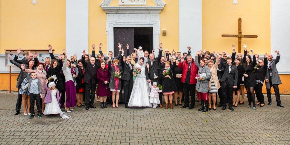 Svatební hosté u kostela.