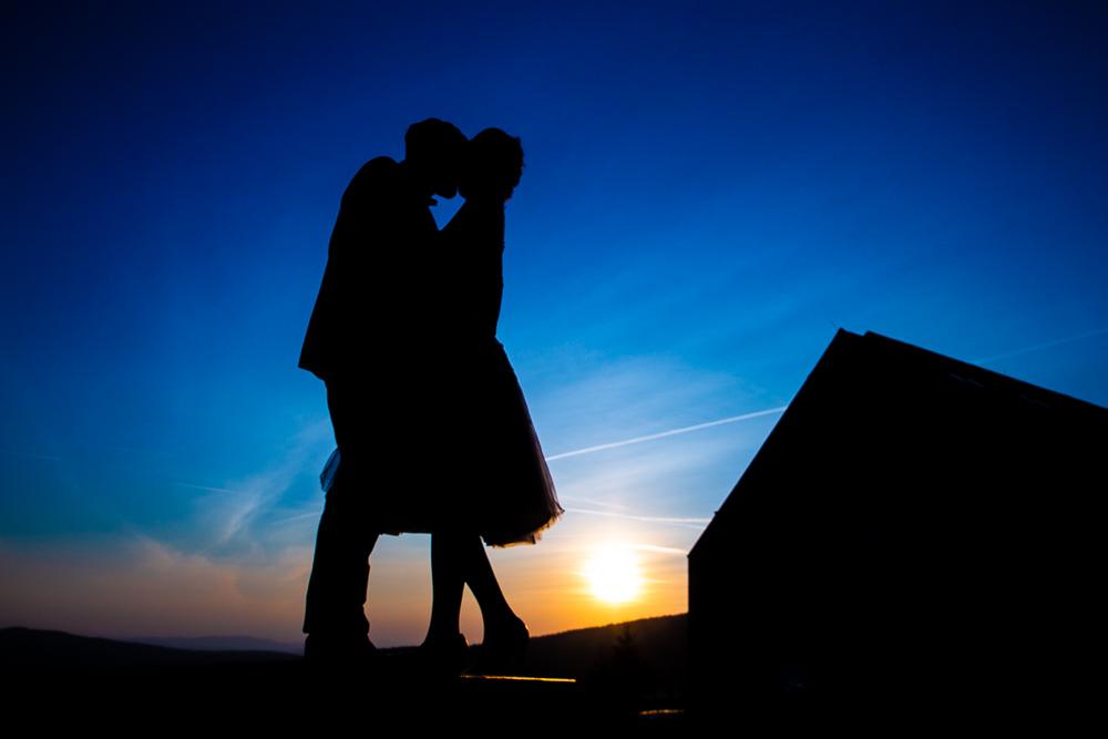 Novomanželé v objetí při západu slunce.