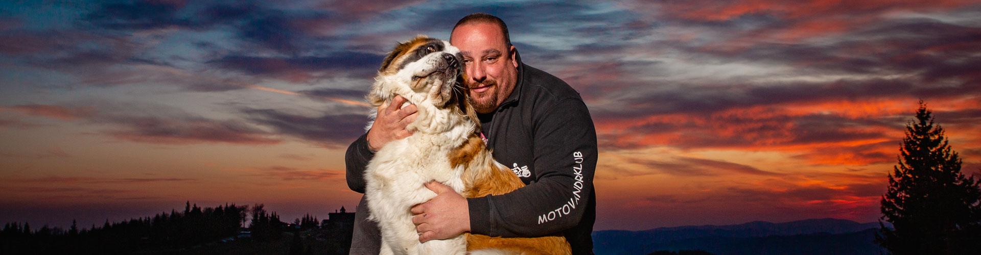 Pes s pánem při západu slunce.