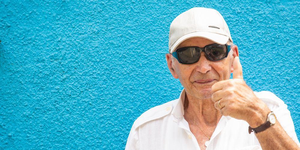 Muž u modré zdi dává palec nahoru.