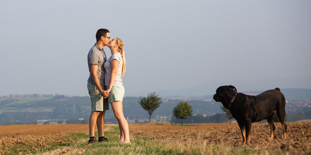 Snoubenci se líbají a pes je pozoruje.