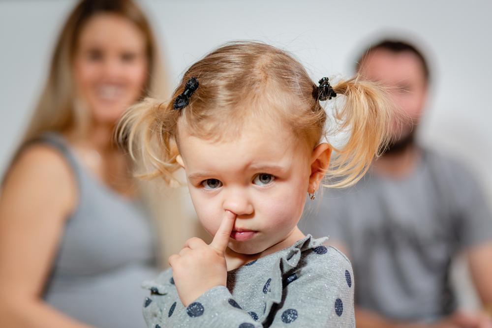 Dítě s rodiči v pozadí.