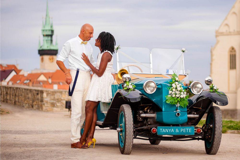 Novomanželé u historického auta.