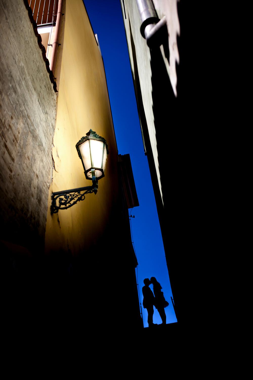 Snoubenci na schodech u hradu v Praze.
