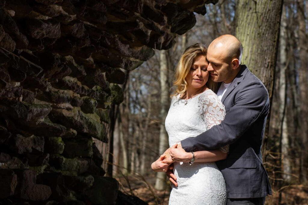 Novomanželé v objetí v lese.