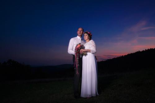 Večerní svatební fotka novomanželů na louce.